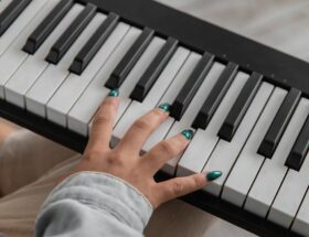 unrecognizable female musician playing synthesizer on couch