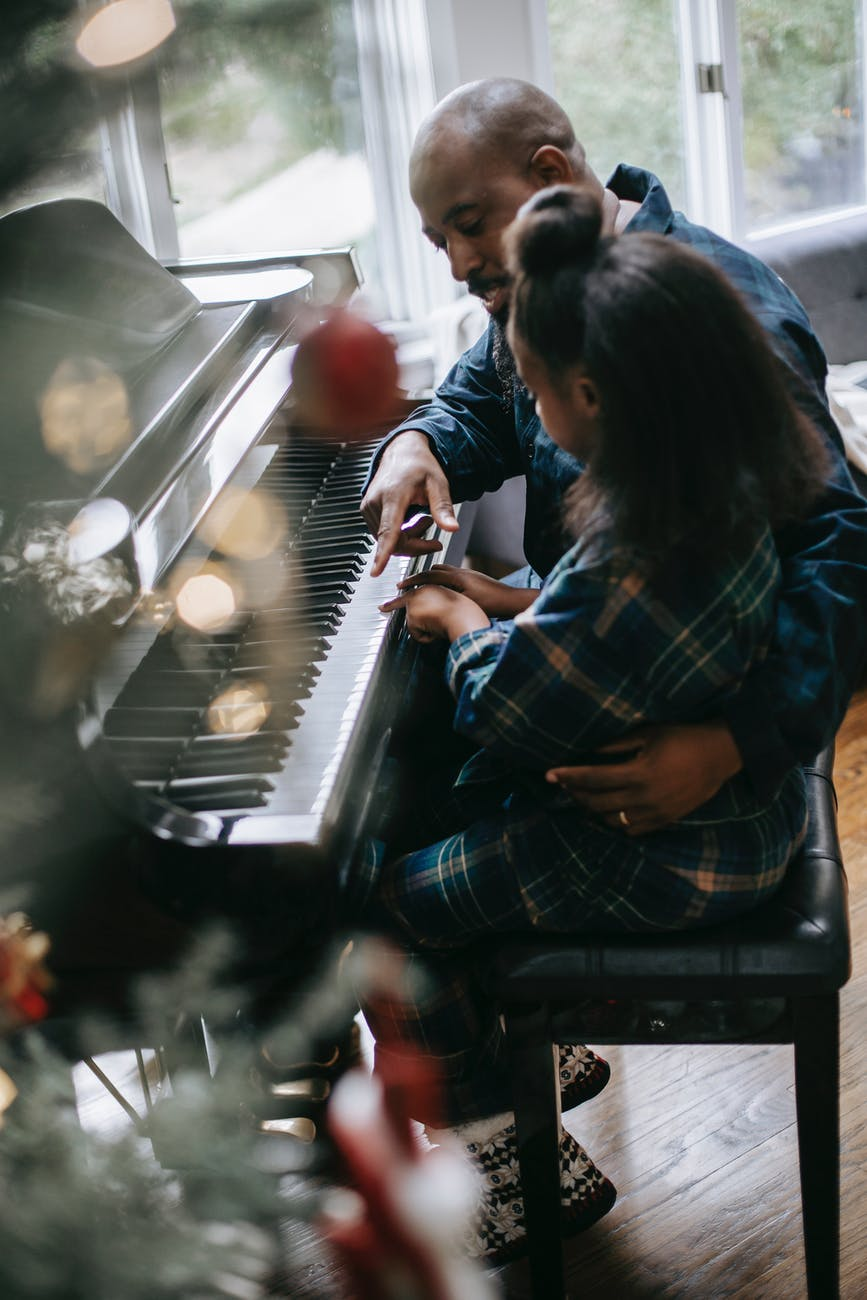 black little girl playing piano with father